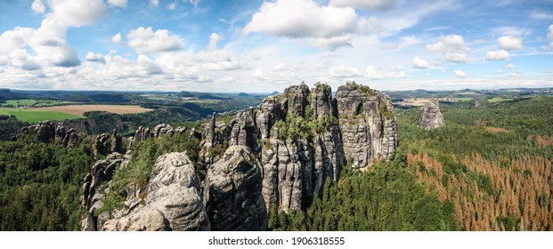 wide panorama of schrammsteine rock-formation in saxon switzerland, elbe sandstone highlands, germany, with blue sky