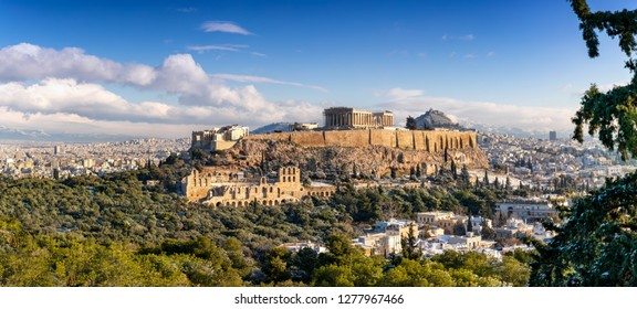 Wide panorama of the skyline of Athens, Greece, featuring the Acropolis and Parthenon Temple covered in light snow during winter time