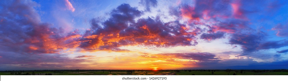Wide panorama of sunset sky with clouds and sunlight over farm