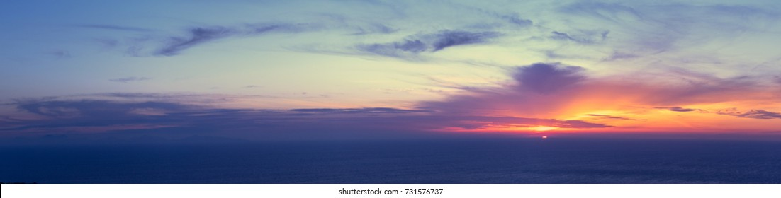 Wide panorama of sunset sky with clouds and golden sunlight over the sea for your idea of web header. Cloudy landscape for background in serenity colors - blue, violet, yellow and pink tone.