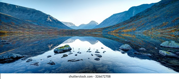 Wide panorama of Tahtarjavr lake with transparent water, rocky bottom and distant mountains reflected in still morning waters, Hibiny mountains above the Arctic circle, Russia