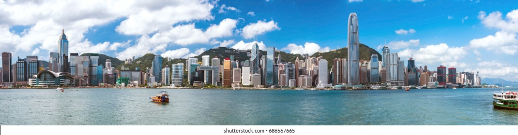 Wide panorama of Victoria harbor on a sunny day in Hong Kong, China