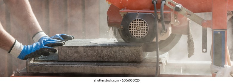 Wide panorama view of a building contractor using an angle grinder outdoors to cut through a paving slab or brick in a cloud of dust.