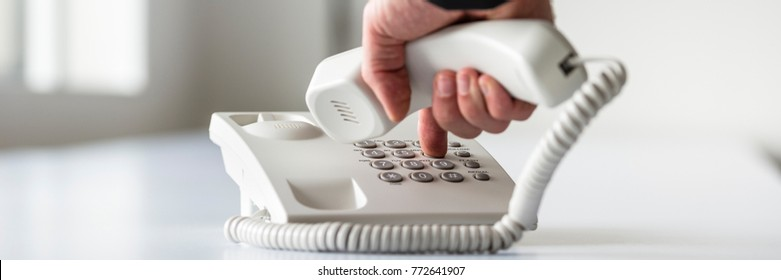 Wide panorama view of a male hand dialing a telephone number in order to make a phone call.