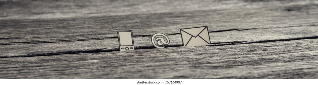 Wide panorama view of at sign, mail and mobile phone icons stuck in between a crack in the wooden surface, toned retro effect.