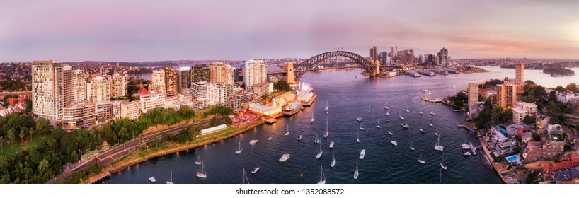 Wide panoramic cityscape of Sydney city CBD landmarks on waterfront of Sydney harbour over Lavender bay from North Shore at sunset.