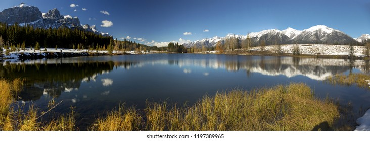 Wide Panoramic Landscape of Blue Quarry Lake and Snowy Rocky Mountain Peaks above City of Canmore near Banff National Park Alberta Canada