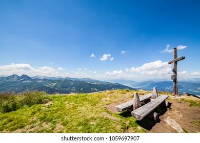 Wide panoramic landscape view from summit of mountain Gasselhoehe with cross and wooden bench to mountain range Dachstein in Styria, Austria