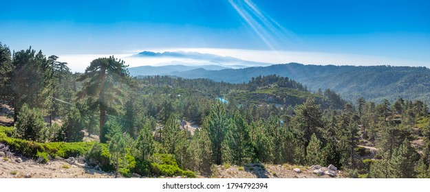 Wide panoramic of the San Bernardino mountains from the top of a local ski resort during the summer, near Running Springs, California with lens flare