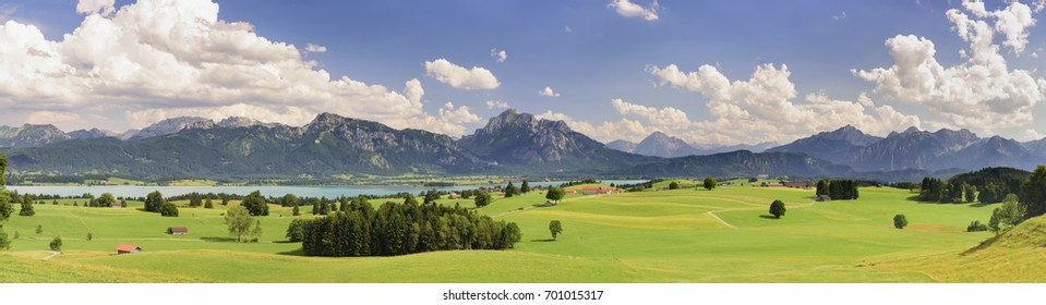 wide panoramic scene with alps mountains, lake and dramatic clouds on sky in Bavaria, germany