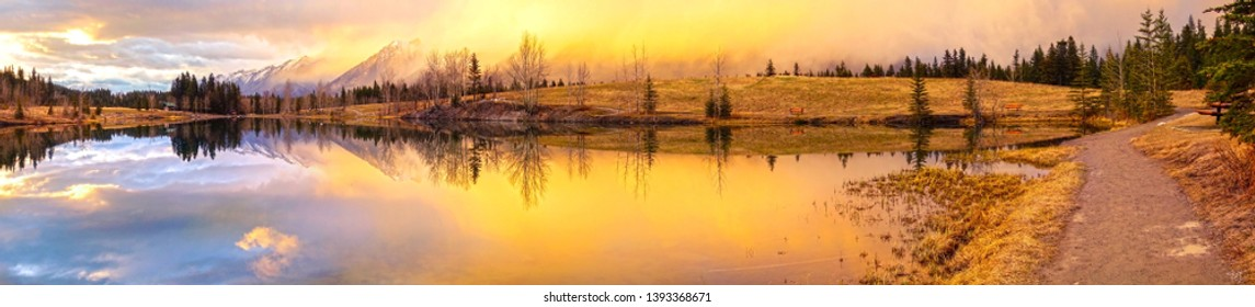 Wide Panoramic Springtime Mountain Landscape and Dramatic Sunset Colors at Quarry Lake above City of Canmore in Alberta Foothills of Canadian Rockies near Banff National Park