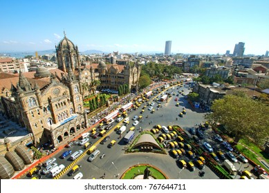 Wide panoramic sweep and bird's eyeview of Chatrapati Shivaji Terminus and surrounding heritage precinct in South Mumbai with statue of Dadabhai Naoroji in the foreground