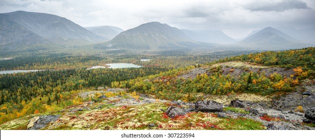 Wide panoramic view of Kunijok valley with mounts and Kukisvumchorr plateau with taiga forest, lakes and tundra in foreground, shot from slope, Hibiny mountains above the Arctic Circle, Russia