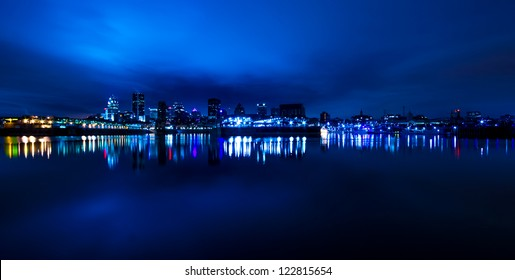 Wide Panoramic View of Montreal, with reflection light in the water, in blue tone at night.