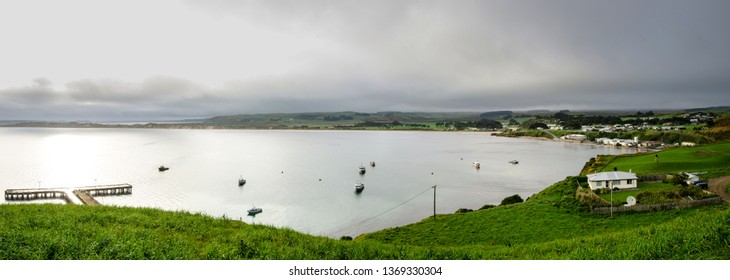 A wide, panoramic view of Petre Bay, Chatham Islands, New Zealand, on a dark, overcast day. Waitangi township on the right, and Waitangi Wharf on the left.