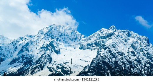 Wide panoramic view of snow covered mountain peak and blue sky with clouds in Baisaran Valley (Mini Switzerland), Pahalgam, Kashmir, India