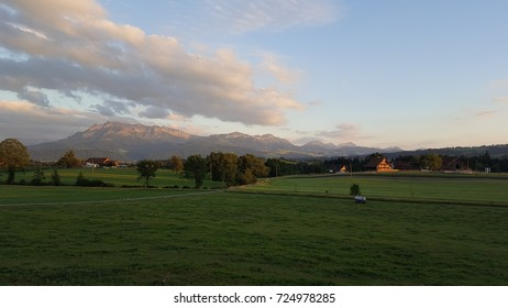 Wide, peaceful Swiss farm with mountains in background.