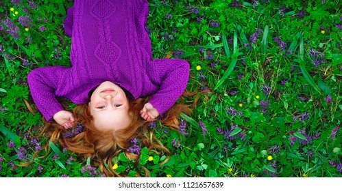 Wide picture of a red haired pretty girl laying on the sping flowers meadow view from the top