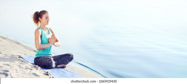 Wide picture of a woman meditating at the beach