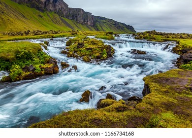 Wide picturesque valley along highway number one  around the island. Powerful cascading waterfalls in Iceland. Travel in July. Concept of active and extreme tourism