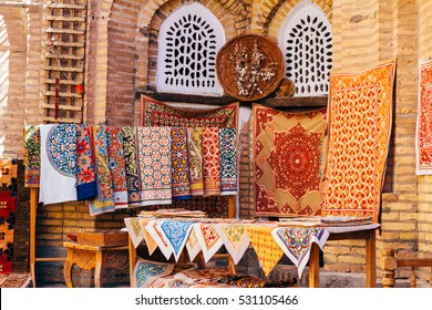 The wide range of the hand made carpets, traditional knotted Uzbek silk rugs, embroidered tablecloths and bed linen in the small bazaar, Khiva, Uzbekistan, Central Asia