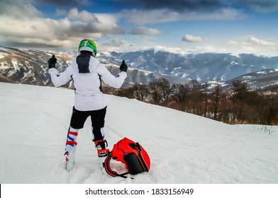 A wide rear view of an Olympic downhill rider in ski gear on top of a snow-capped mountain. In front of a beautiful landscape with blue clouds
