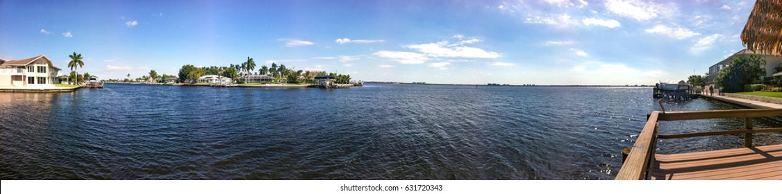 A wide river with houses and blue sky in Cape Coral, Florida