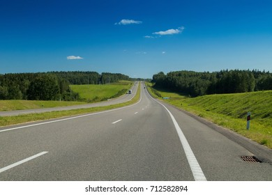 A wide road, green trees and a dark sky with gray clouds