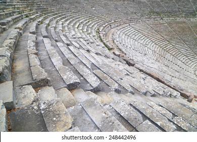 Wide rows of stone tribunes in ancient amphitheater, Epidaurus, Greece