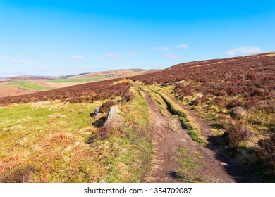 A wide rutted footpath crosses the Derbyshire Peak District on a bright spring morning