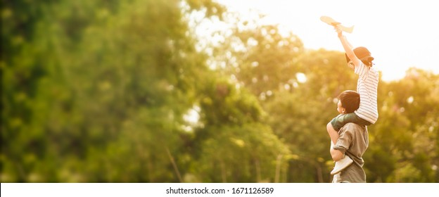Wide screen of Asian father put his son on his shoulder to play paper plane, spending time together at park in autumn afternoon sunlight, the concept father's day, daddy hero, Family background.