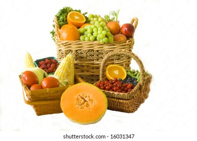 A wide selection of organic produce in baskets over a white background.