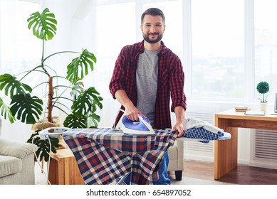 Wide shot of appealing brunet ironing clothes on ironing board