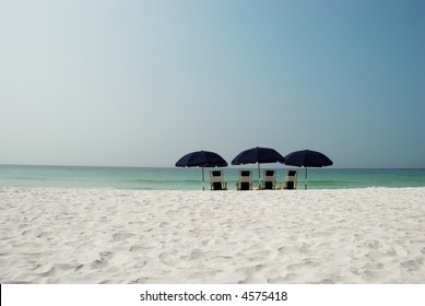Wide shot of beach umbrellas and white sand in foreground