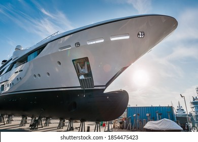 Wide shot of the bow of a new  white modern superyacht on dry dock, with a bulbous bow on a sunny day, with stainless steel  anchor on a sunny day with blue sky
