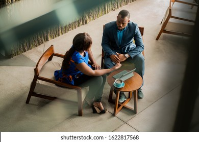 Wide shot business meeting consultation by black african financial adviser.