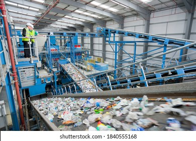 Wide shot of Businessman and worker talking on platform above conveyor belts in recycling plant