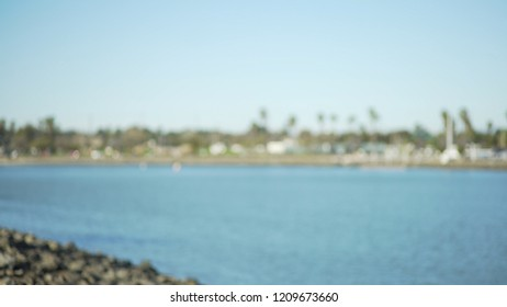 Wide shot of calm bay with oceanfront homes and palm trees