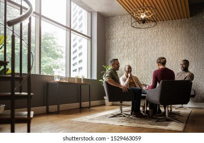Wide shot of casual seated diverse business meeting in modern open workspace with large windows and sunlight shining in