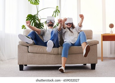 Wide shot of delightful couple driving in VR glasses while sitting on sofa