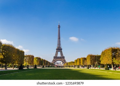 Wide shot of the Eiffel Tower in Paris seen from the lawn of the Champ de Mars one autumn day by a clear blue sky