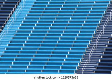 Wide shot of empty, blue bleachers.