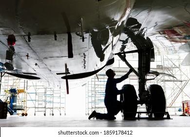 Wide shot of an engineer inspecting the landing gear of a passenger jet at a hangar.