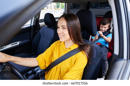 Wide shot of female driving car with son sitting in baby seat