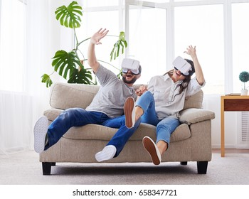 Wide shot of gorgeous girl and boy playing in virtual reality goggles while sitting on sofa