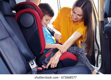 Wide shot of gorgeous mom helping son sitting in baby seat to fasten seat belt