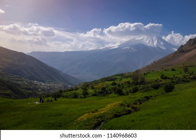 A wide shot of a grassy plain and Damavand mountain is in the background.