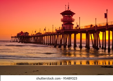 A wide shot of the Huntington Beach Pier during a bright red and orange sunset.