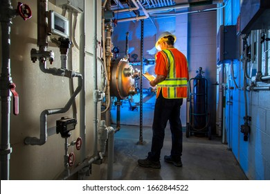 Wide shot of Industrial scene lit blue with pipes ,guages and valves. A man wearing goggles, hard hat, and orange safety vest holds a clipboard and looks at gauge to inspect .