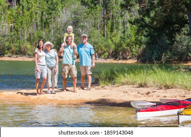 Wide shot of a multi-generation family standing at the lakeside with kayaks and smiling at the camera. - Shutterstock ID 1859143048